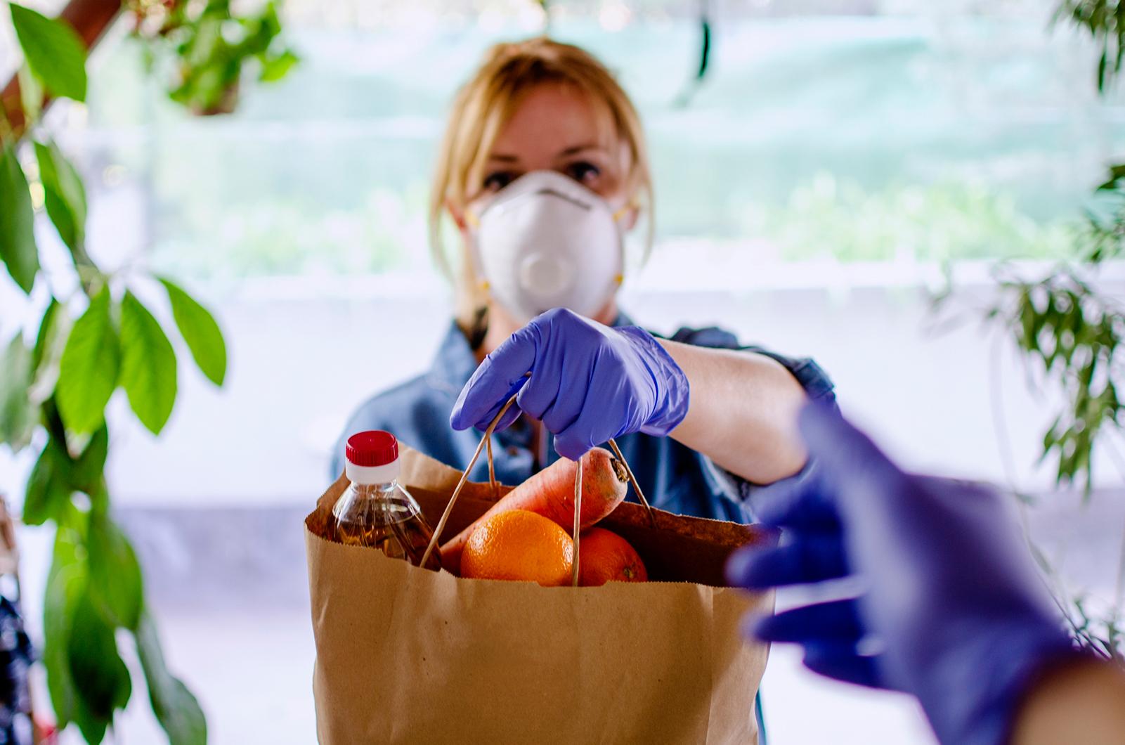 A volunteers handing food basket